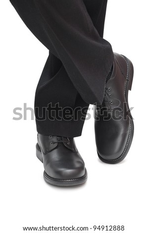 Man's feet in black trousers and black shoes. Isolated on white background. - stock photo