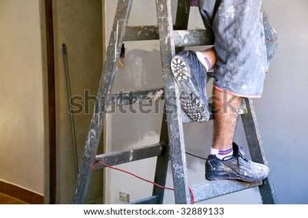 Man's feet on a ladder, in a construction site. - stock photo