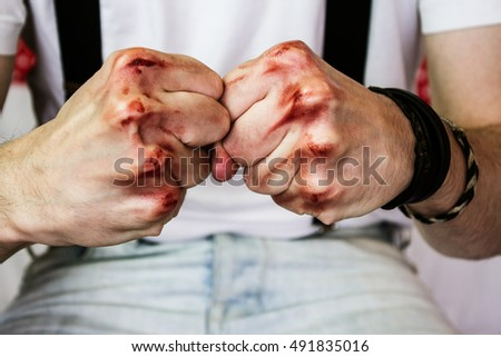 man's fists with blood