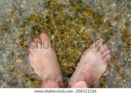 man's foot standing on stones in a river - stock photo