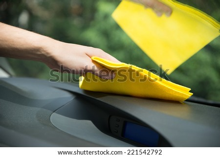 Man's hand cleaning car interior with yellow microfiber cloth - stock photo