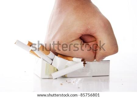 Man's hand crushing cigarettes - stock photo