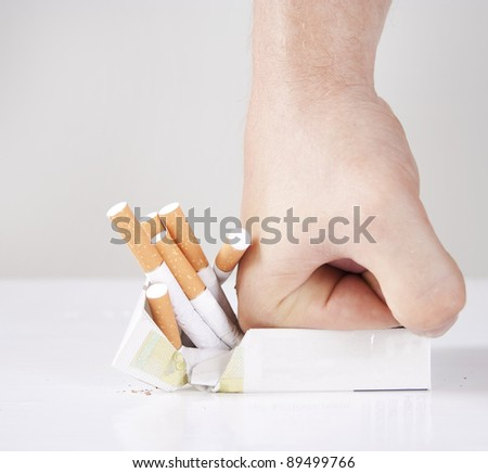 Man's hand crushing cigarettes - stock photo