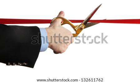 Man's hand cutting red ribbon with pair of scissors isolated on white - stock photo
