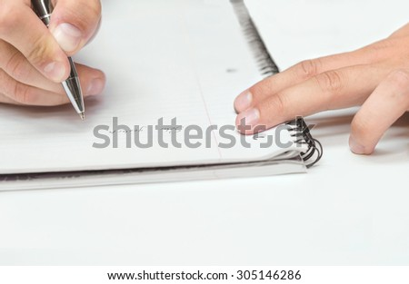Man's hand drawing in a notebook