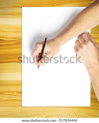 Man's hand draws on white paper on wooden desk - stock photo
