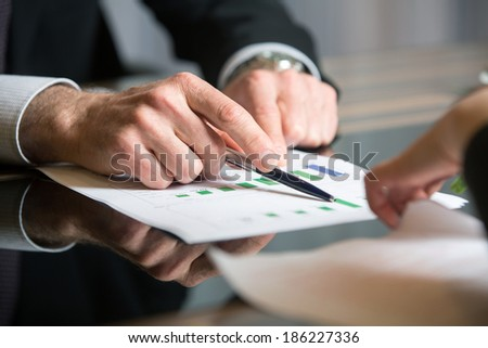 Man's hand holding a black pen pointing at the diagram on a meeting dedicated to financial analysis - stock photo
