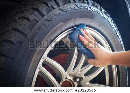 Man's hand holding a blue fabric cleaning car tires and wheels