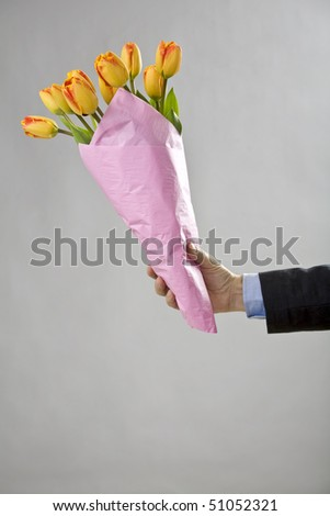 Man's hand holding a bouquet of orange tulips - stock photo