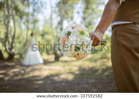 man's hand holding a bridal bouquet, the background blurred silhouette of a bride - stock photo
