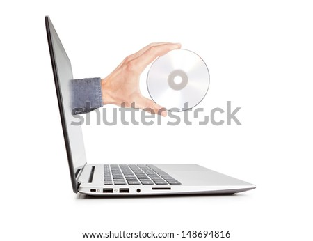 Man's hand holding a disk sticking out of the notebook. Concept of technology. - stock photo
