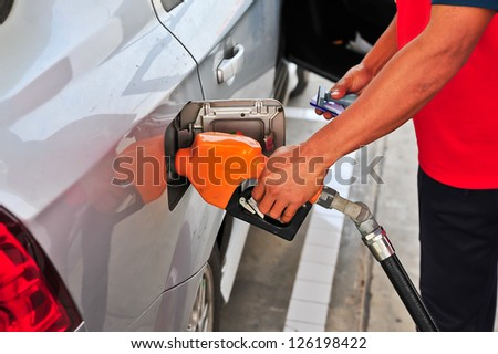 Man's hand holding a gas pump - stock photo