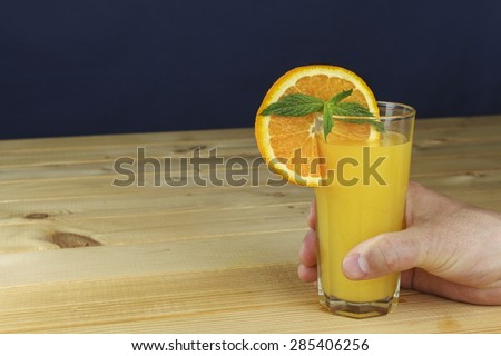 Man's hand holding a glass of juice on a wooden table. Blue blurred background. - stock photo