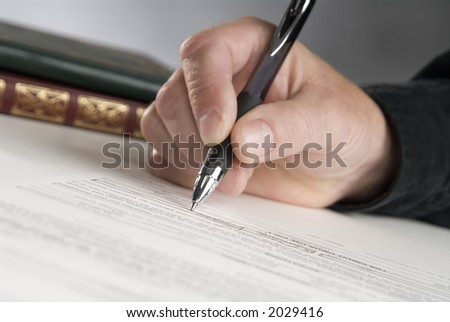 man's hand holding a pen writing,books in background