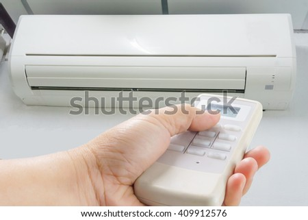 Man 's hand holding a remote control to turn on the air conditioner