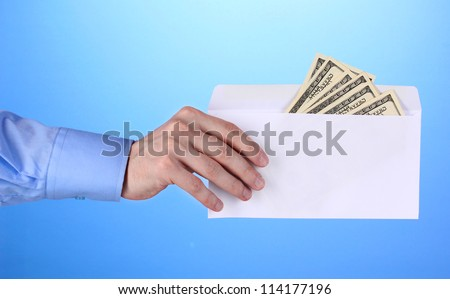 man's hand holding an envelope with dollars on blue background - stock photo