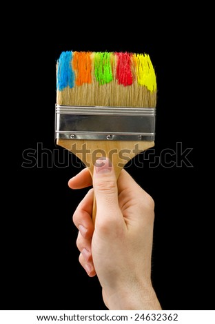 man's hand holding big brush with different colors of paint;choosing colors - stock photo