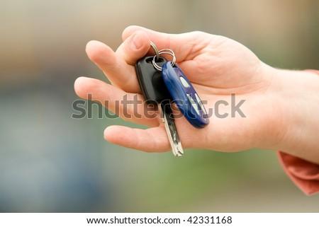Man's hand holding car keys - stock photo