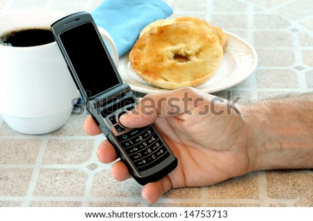Man's hand holding cell phone ready to dial while sitting at breakfast table. - stock photo