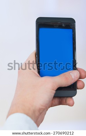 man's hand holding cell phone with empty blue screen copy space - stock photo