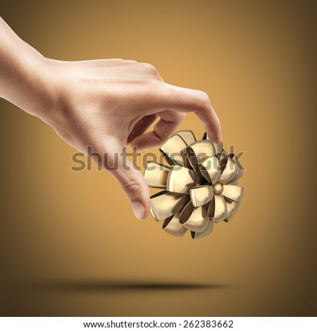 Man's hand holding golden Bow. High resolution 3D collection of gold objects.  - stock photo