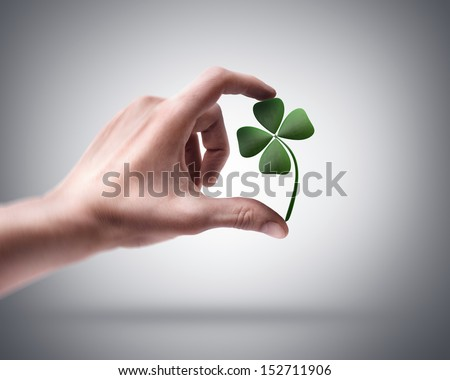 Man's hand holding green clover - stock photo