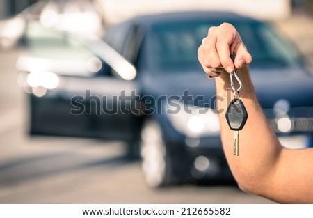 Man's hand holding modern car keys ready for rental - Concept of transportation with automobile second hand sale and trade - stock photo