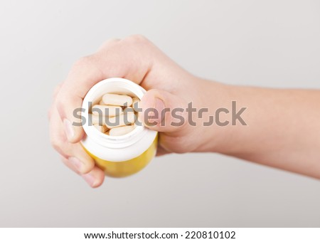 Man's hand holding opened container with white pills  - stock photo
