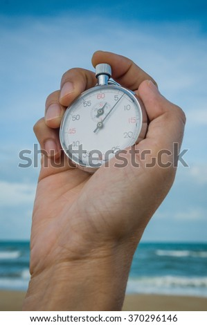 Man's hand holding stopwatch with blue sky - stock photo