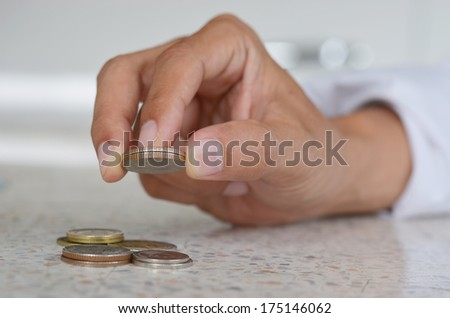 man's hand, holding two coin