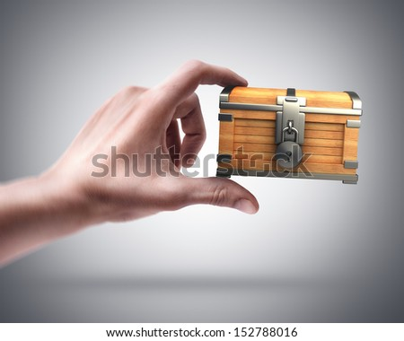 Man's hand holding vintage chest with lock - stock photo