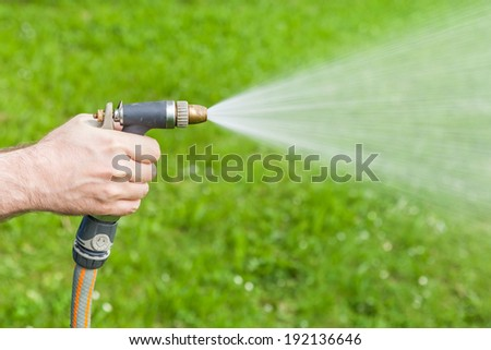 Man's hand holding water sprinkler while gardening, water spraying out of sprinkler on the grass - stock photo