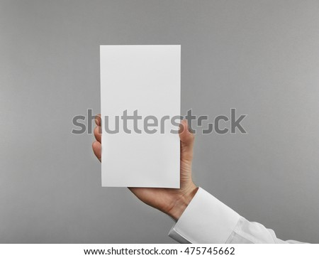 Man's hand holding white paper on light background