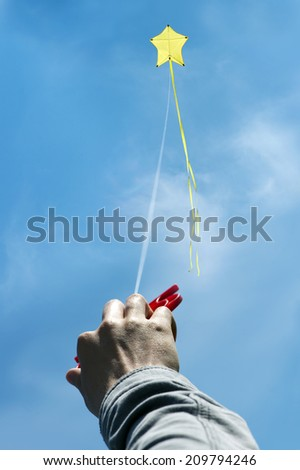 Man's hand holding yellow star kite flying against blue sky - stock photo