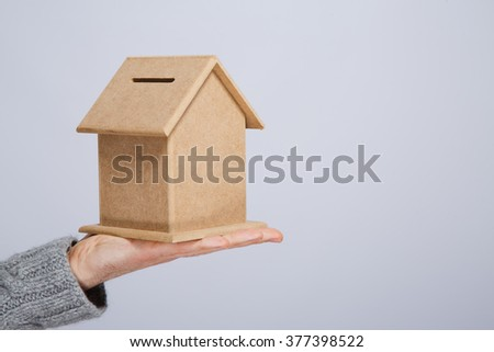 Man's hand in gray sweater holding little wooden house money box at gray studio background, close up, mock up, copy space.