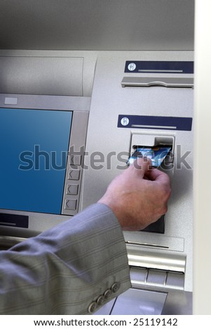 man's hand inserting card into cash dispense - stock photo