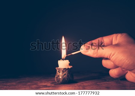 Man's hand is lighting a candle - stock photo