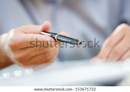Man's hand making accent gesture or pointing at something with a black pen during a meeting or negotiation