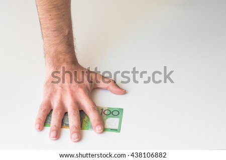 Man's hand on Australian Dollar banknote