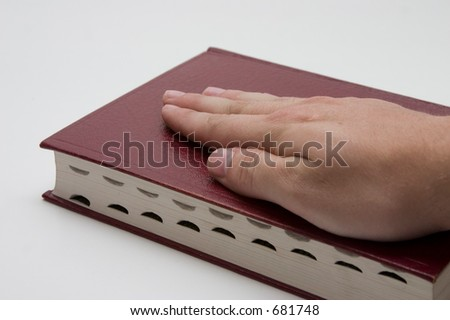 Man's hand on the Bible - stock photo