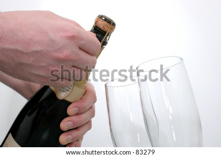 Man's hand opening a bottle of champagne next to two champagne flutes shot on white.