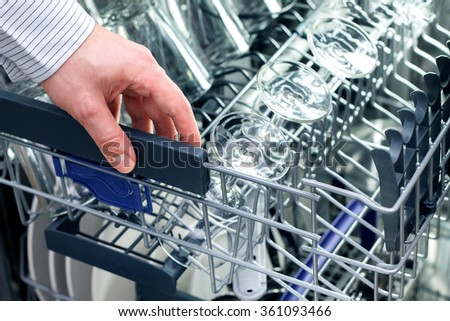 Man's hand opening dishwasher with clean utensils - stock photo