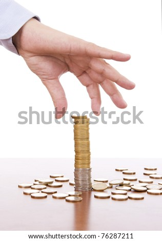 Man´s hand picking coins from a stack - stock photo