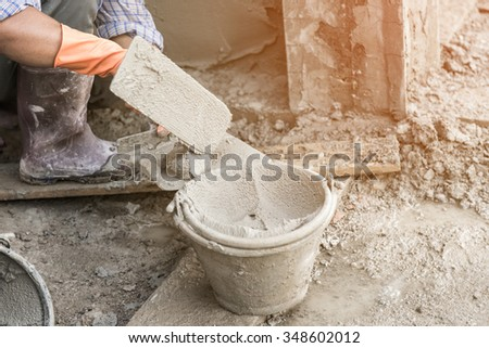 man's hand plastering a wall with trowel. - stock photo