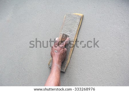 Man's hand plastering a wall with trowel. Construction worker. Masonry tool. Construction industry. Selective focus. - stock photo