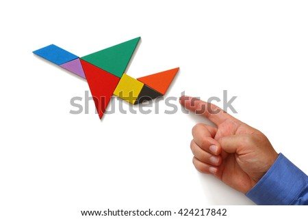 man's hand pointing at plane made from square tangram puzzle, white isolated background