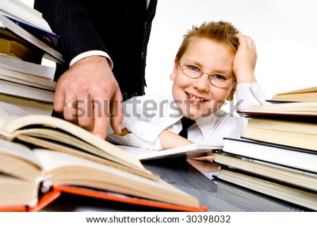 Man's hand pointing to school books, forcing boy to learn . Isolated
