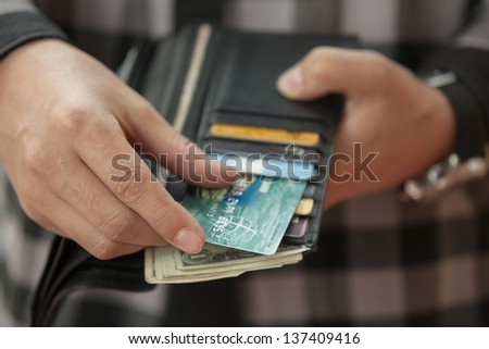 Man's hand pulls out a credit card from a black purse - stock photo