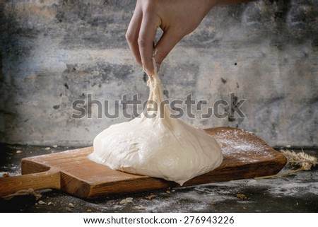 Man's hand pulls the dough for pizza on wooden cutting board over dark kitchen table, powdered with flour. - stock photo