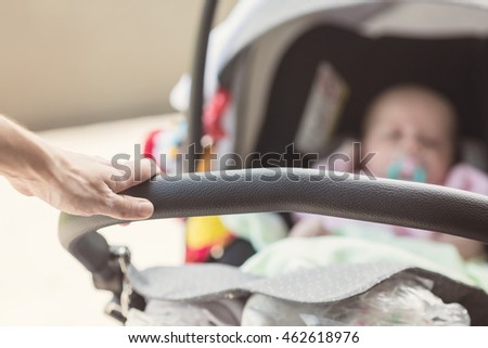 Man's hand pushing the child stroller with the newborn baby laying inside